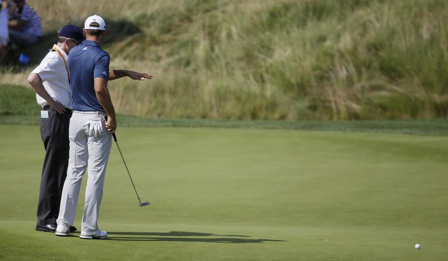 FILE - In this June 19, 2016, file photo, Dustin Johnson, right, talks to a rules official on the fifth green during the final round of the U.S. Open golf tournament at Oakmont Country Club in Oakmont, Pa. Top rules experts from around the world have been meeting privately the last five years to simplify the rules in what could be the most expansive rules overhaul ever. (AP Photo/John Minchillo, File)