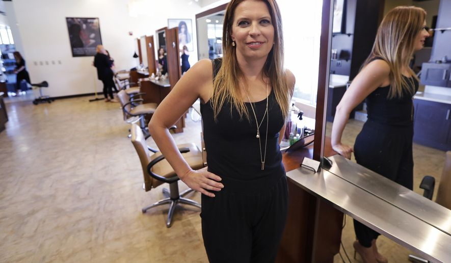 In this Tuesday, Aug. 23, 2016, photo, Christine Perkins, who owns Pyara Spa and Salons at two locations in the Boston area, poses at a stylist station at her salon in Burlington, Mass. Perkins struggles to find candidates to style hair, do manicures and give massages, in part because some beauty schools in the region have closed. (AP Photo/Charles Krupa)
