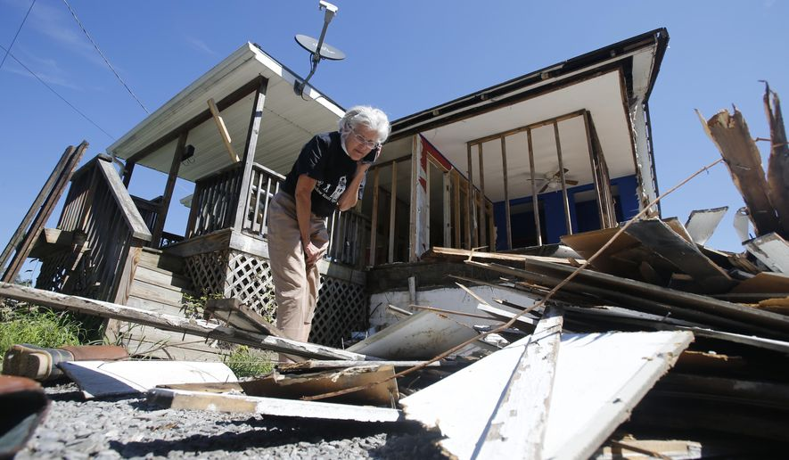 "Mayor Andrea ""Andy"" Pendleton, looks through debris from a flood ravaged home in Rainelle, W.Va., on Tuesday, Aug. 23, 2016. The town of 1,500 was badly battered during the late June floods that killed 23 people statewide. (AP Photo/Steve Helber)"