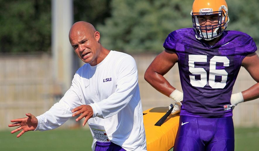 In this Aug. 6, 2016, photo, LSU defensive coordinator Dave Aranda gives instructions to Tigers M.J. Patterson during an NCAA college football practice in Baton Rouge, La.  Wisconsin's marquee season opener on Saturday against No. 5 LSU features a unique wrinkle. The Badgers will face their old defensive coordinator in Dave Aranda, who took the same job with the Tigers. (Brett Duke/NOLA.com The Times-Picayune via AP)