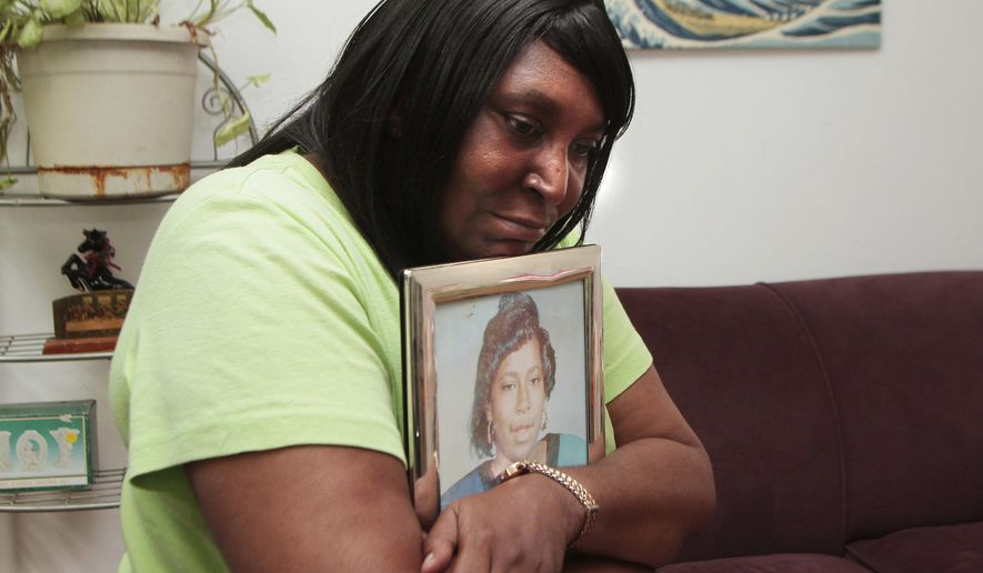 """In this Wednesday, Aug. 31, 2016, photo, Theresa Matthews, of Dixmoor, Ill., holds a framed photo of her daughter, Cateresa Matthews, who was kidnapped and murdered in 1991. Prosecutors said Willie Randolph will be charged Thursday, Sept. 1, 2016, with murder and kidnapping in the suburban Chicago girl's death. More than two years ago, five men reached a settlement with Illinois State Police after they were cleared of all charges in the death of Matthews. The men, known as the """"Dixmoor Five,"""" spent a decade or more in prison before DNA evidence pointed to Randolph. (Leslie Adkins/Chicago Sun-Times via AP)"""