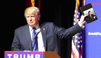 """Donald Trump holds up a copy of his 1987 best-seller """"The Art of the Deal"""" at a New Hampshire rally to emphasize his business talents. (Associated Press) ** FILE **"""