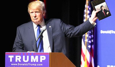 """Donald Trump holds up a copy of his 1987 best-seller """"Art of the Deal"""" at a New Hampshire rally to emphasize his business talents. (Associated Press)"""