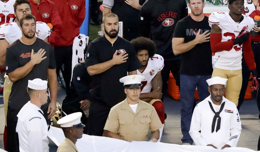 San Francisco 49ers quarterback Colin Kaepernick, middle, kneels during the national anthem before the team's NFL preseason football game against the San Diego Chargers, Thursday, Sept. 1, 2016, in San Diego. (AP Photo/Chris Carlson)