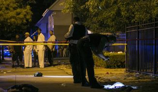 In this Aug. 7, 2016, photo, Chicago police investigate a scene in Chicago where gunfire at a birthday party left a man dead and a woman injured. The city's police department said Thursday, Sept. 1, 2016, Chicago recorded 90 homicides in August, its highest monthly death toll in two decades. (Ashlee Rezin /Chicago Sun-Times via AP)