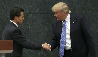 In this Aug. 31, 2016, photo, Mexico's President Enrique Pena Nieto and Republican presidential nominee Donald Trump shake hands after a joint statement at Los Pinos, the presidential official residence, in Mexico City. (AP Photo/Marco Ugarte)