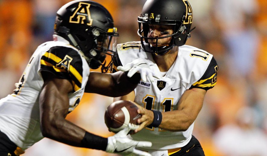 Appalachian State quarterback Taylor Lamb (11) hands the ball off to running back Jalin Moore during the first half of an NCAA college football game against Tennessee Thursday, Sept. 1, 2016 in Knoxville, Tenn. (AP Photo/Wade Payne)