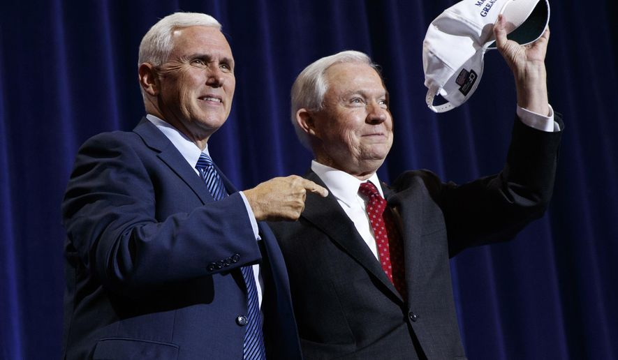 """Republican vice presidential candidate Gov. Mike Pence, R-Ind., left, stands with Sen. Jeff Sessions, R-Ala., as he holds up a hat that says """"Make Mexico Great Again Also"""" during a campaign event with Republican presidential candidate Donald Trump at the Phoenix Convention Center, Wednesday, Aug. 31, 2016, in Phoenix. (AP Photo/Evan Vucci)"""