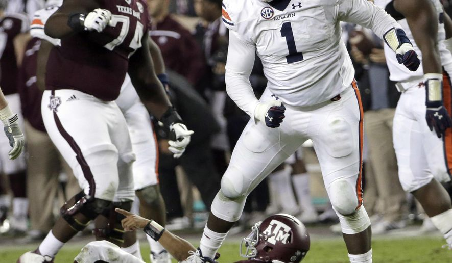 FILE - In this Nov. 7, 2015, file photo, Auburn defensive tackle Montravius Adams (1) celebrates after sacking Texas A&M quarterback Kyler Murray, bottom, during the second quarter of an NCAA college football game, in College Station, Texas. Auburn's defensive line is one of the best in the Southeastern Conference, judging it solely on recruiting rankings. (AP Photo/David J. Phillip, File)