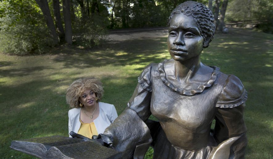 CORRECTS TO CLARIFY WILSON IS CONSIDERED THE FIRST FEMALE AFRICAN AMERICAN NOVELIST - In this photo taken Thursday, Aug. 25, 2016, JerriAnne Boggis stands next to a statue of Harriet Wilson in Milford, N.H. Wilson, who was born in Milford, is considered the first female African-American to publish a novel on the North American continent. Boggis is part of a group of African-American and white scholars who are working on what they hope will be a statewide, black history trail that recognizes African-American contributions. (AP Photo/Jim Cole)