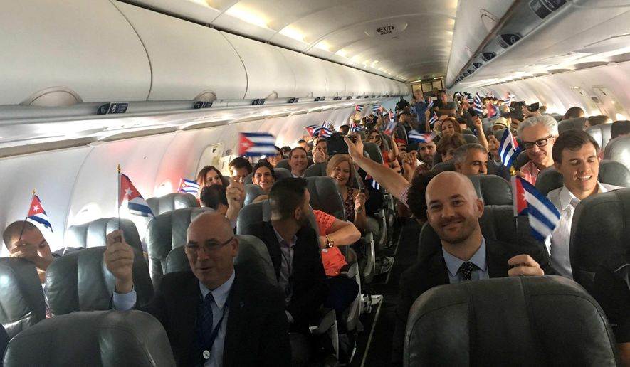 JetBlue flight 387 passengers hold up representations of Cuba's national flag, just before touching down at the airport in Santa Clara, Cuba, Wednesday, Aug. 31, 2016. JetBlue 387, the first commercial flight between the U.S. and Cuba in more than a half century, landed in the central city of Santa Clara on Wednesday morning, re-establishing regular air service severed at the height of the Cold War. (AP Photo/Michael Weissenstein)