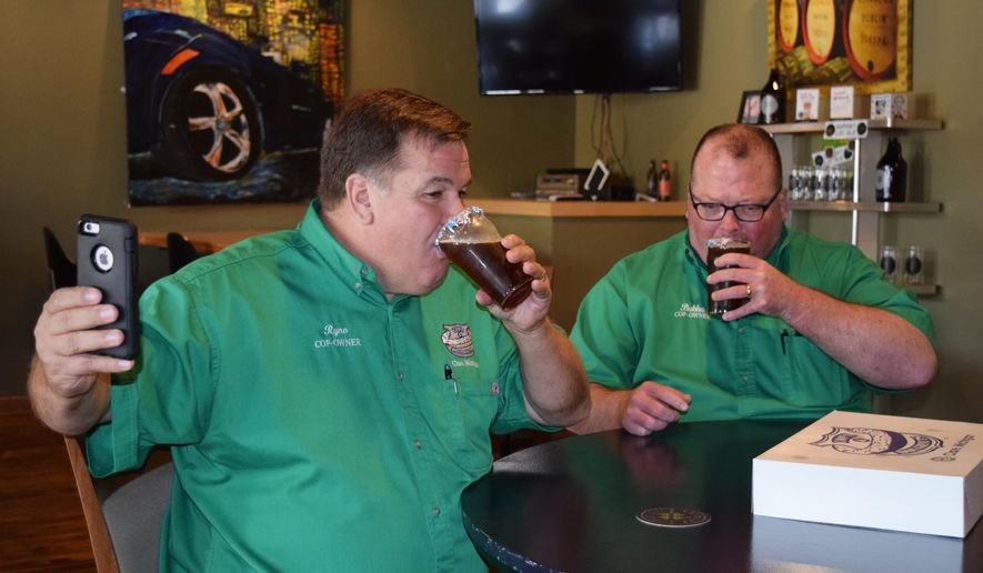 In this Wednesday, Aug. 31, 2016, photo, Cops & Doughnuts President Greg Rynearson, left, and Vice President Al White, both retired Clare Police officers, take their first sips of 'Hoppy Cop' beer at Four Leaf Brewing in Clare, Mich. The northern Michigan brewery paired with a bakery to create two new doughnut-infused beers. (Sue Field/The Morning Sun via AP)