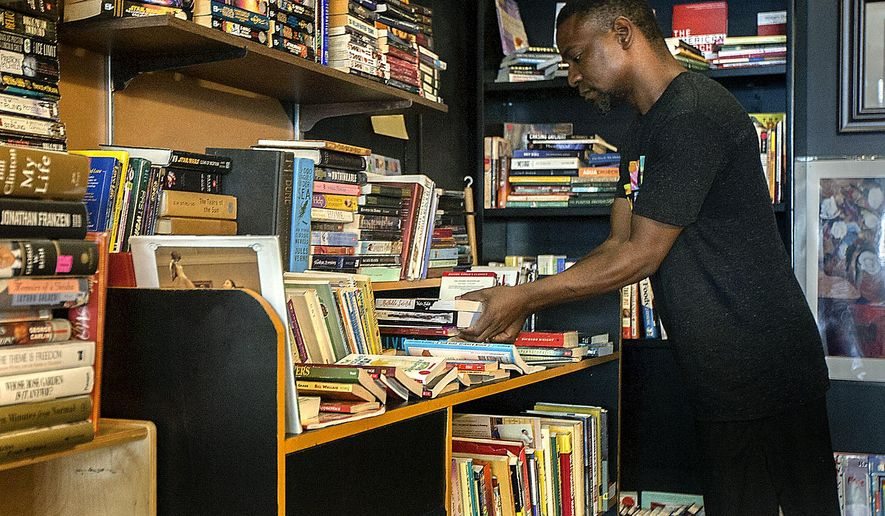 In this Aug. 8, 2016 photo, Common Grounds owner, Jeff Foster puts out new  books at his coffee shop in DeKalb, Ill. Foster has plans to organize a mentor program through the coffee shop to encourage young, creative kids in the area to pursue art and education. (Katie Smith/Daily Chronicle via AP)