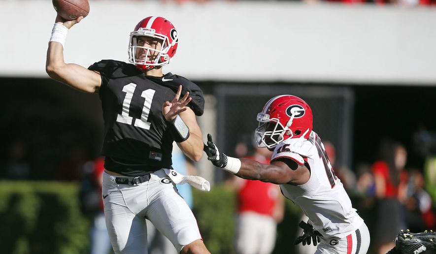 FILE - In this April 16, 2016, file photo, Georgia quarterback Greyson Lambert (11) throws under pressure from linebacker D'Andre Walker (15) during the second half of the NCAA college football team's spring game, in Athens, Ga. Senior Greyson Lambert will start at quarterback for No. 18 Georgia in its season opener against No. 22 North Carolina, getting the nod over touted freshman Jacob Eason. Georgia spokesman Claude Felton confirmed Thursday, Sept. 1, that Lambert had beaten out Eason for the starting job.(AP Photo/John Bazemore, File)