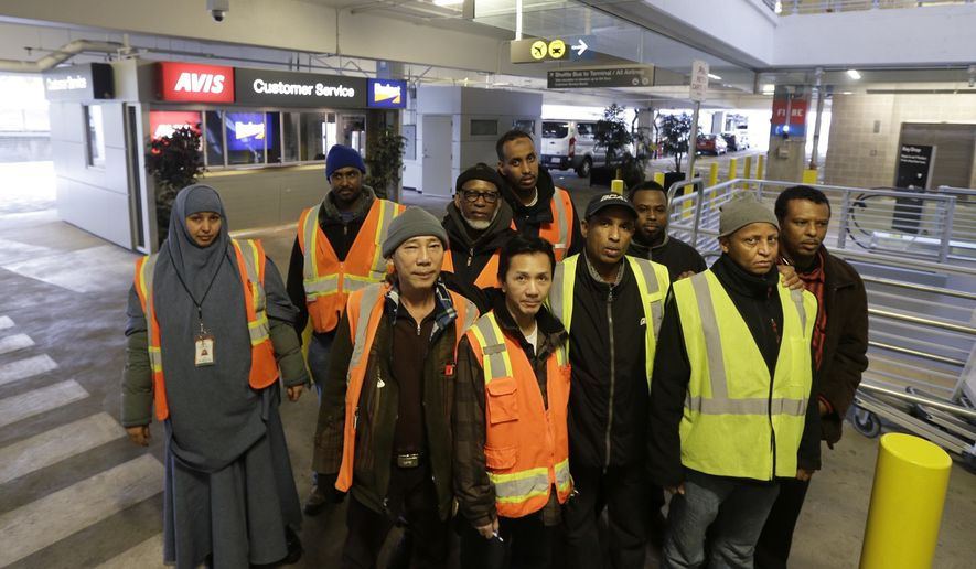 FILE- In this Feb. 17, 2016, file photo, a group of people who work at the rental car facility at Seattle-Tacoma International Airport and are suing their employers over the $15 minimum wage they say they have not been paid, pose for a photo in Seattle, Wash, while on break at their workplace. Two companies that provide baggage and other services at Seattle-Tacoma International Airport have agreed to pay more than $10 million to settle allegations that they ignored the nation's first $15 minimum wage law after it took effect. (AP Photo/Ted S. Warren, file)