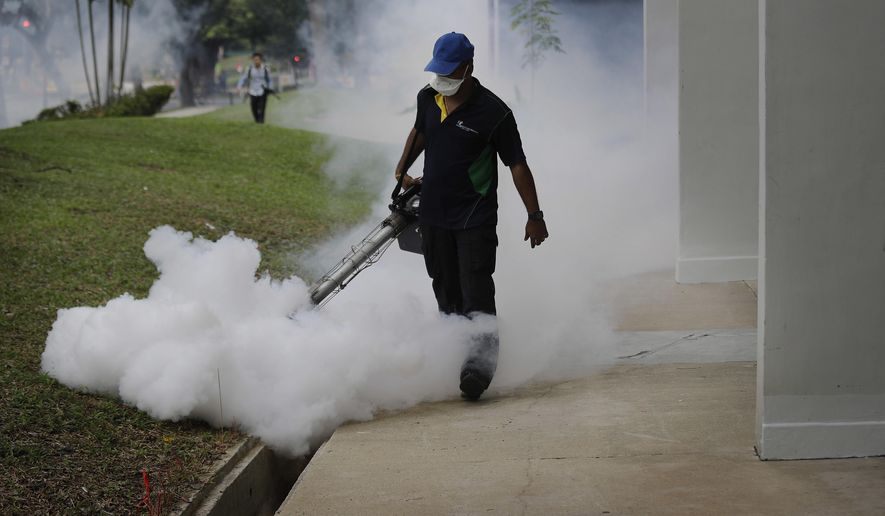 A pest control worker fumigates drains at a local housing estate where the latest case of Zika infections were reported from on Thursday, Sept. 1, 2016 in Singapore. Scientists trying to predict the future path of Zika say that 2.6 billion people living in parts of Asia and Africa could be at risk of infection, based on a new analysis of travel, climate and mosquito patterns in those regions.  (AP Photo/Wong Maye-E)