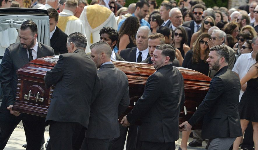 FILE - In this Aug. 6, 2016 file photo, mourners carry the casket of Karina Vetrano from St. Helen's Church following her funeral in the Howard Beach section of the Queens borough of New York. Detectives hunting for the person who strangled Vetrano in a secluded New York City marsh were encouraged after genetic material found beneath her fingernails, on her phone and on her neck resulted in a DNA profile of her probable attacker. A month later, their optimism has waned. The genetic fingerprint didn't match any of the profiles from convicted criminals in the state's Combined DNA Index System. A check against the FBI's DNA database also came up empty. (Steven Sunshine  /Newsday via AP)