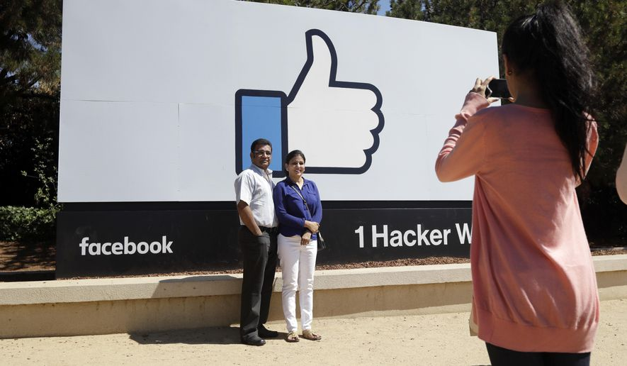 In this Aug. 31, 2016, photo, visitors take photos in front of the Facebook logo outside of the company's headquarters in Menlo Park , Calif. (AP Photo/Marcio Jose Sanchez) ** FILE **