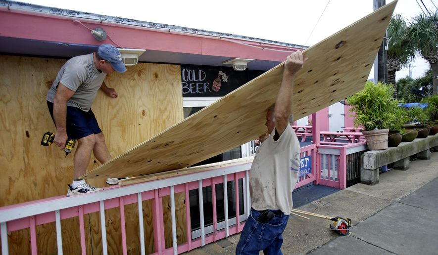 Tim Allen, left, and Joe Allen board up the front of an outdoor bar as they prepare for Tropical Storm Hermine Thursday, Sept. 1, 2016, in Cedar Key, Fla. (AP Photo/John Raoux)