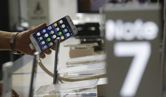 A customer holds a Samsung Electronics Galaxy Note 7 smartphone at the headquarters of South Korean mobile carrier KT in Seoul, South Korea, Friday, Sept. 2, 2016. Samsung will issue a global recall of the Galaxy Note 7 smartphone as soon as this weekend after its investigation on explosion claims found batteries were at fault, according to South Korea's Yonhap News. (AP Photo/ahn Young-joon)