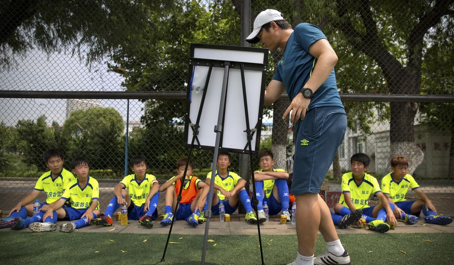 In this Monday, Aug. 1, 2016, photo, Yanbian, China, coach Zhang Yanmao gives instructions to his team during halftime of a game against a team from Myanmar in a youth soccer tournament in Qinhuangdao in northern China's Hebei Province. China is mobilizing under President Xi Jinping's drive to overhaul football in China and turn its team from a national embarrassment into a World Cup winner by 2050. (AP Photo/Mark Schiefelbein)