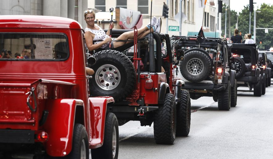 In this Aug. 13, 2016 photo, Angie Gray of Temperance, Mich., rides in the back of a 1994 Jeep YJ owned by her parents, Craig and Diana Grover, during a parade in Toledo, Ohio. The city held a Jeep Fest to celebrate the Jeep brand's 75th anniversary. (Andy Morrison/The Blade via AP)