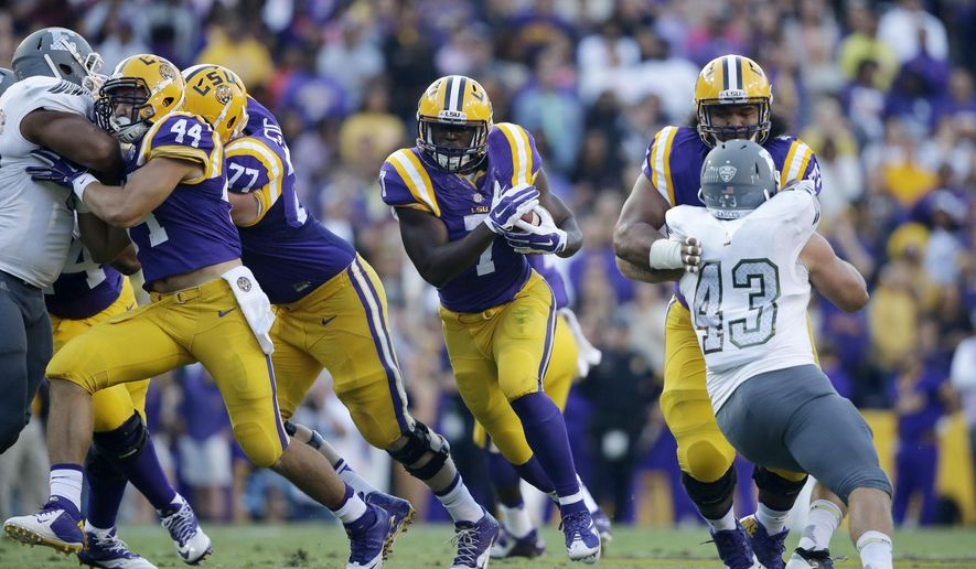 FILE - In this Oct. 3, 2015, file photo, LSU running back Leonard Fournette (7) carries past Eastern Michigan linebacker Anthony Zappone (43) in the first half of an NCAA college football game in Baton Rouge, La. Wisconsin and LSU are teams in transition in the trenches. The Badgers could start the season with four sophomores and a new left tackle up front on Saturday, Sept. 3, 2016. The fifth-ranked Tigers will debut with two new tackles blocking for Heisman Trophy hopeful Leonard Fournette. (AP Photo/Gerald Herbert, File)