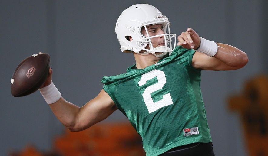 FILE - In this Tuesday, Aug. 2, 2016 file photo, Oklahoma State quarterback Mason Rudolph throw during an NCAA college football practice in Stillwater, Okla. Oklahoma State's strong performance last season and the return of 18 starters have earned the Cowboys a slightly better starting position this year, a No. 21 preseason ranking. (AP Photo/Sue Ogrocki, File)