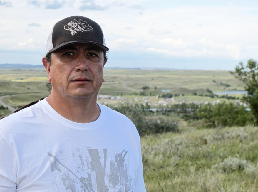 In this Aug. 26, 2016, photo, Standing Rock Sioux Chairman Dave Archambault II poses for a photo near Cannon Ball., N.D., on the Standing Rock Sioux Reservation overlooking an encampment where Native Americans from across North America have gathered to join his tribe's growing protest against a $3.8 billion four-state oil pipeline. About 30 people, including Archambault himself, have been arrested in recent weeks for interfering with construction of the Dakota Access pipeline. (AP Photo/James MacPherson) ** FILE **