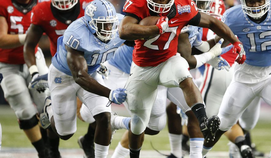 Georgia running back Nick Chubb (27) tries to breaks away from North Carolina linebacker Andre Smith (10) in the first of an NCAA college football game against North Carolina in Atlanta, Saturday, Sept. 3, 2016. Chubb missed most of last season with a knee injury. (AP Photo/John Bazemore)
