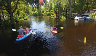 Residents evacuate the Elfers Parkway area of Pasco County, Fla., flooded by the overflowing Anclote River, in Elfers, Fla., Sunday, Sept. 4, 2016. The Anclote River northwest of Tampa was forecast to go well into major flood stage on Sunday afternoon. Emergency managers issued mandatory evacuations for some low-lying mobile home parks and apartment buildings. (Luis Santana/Tampa Bay Times via AP)