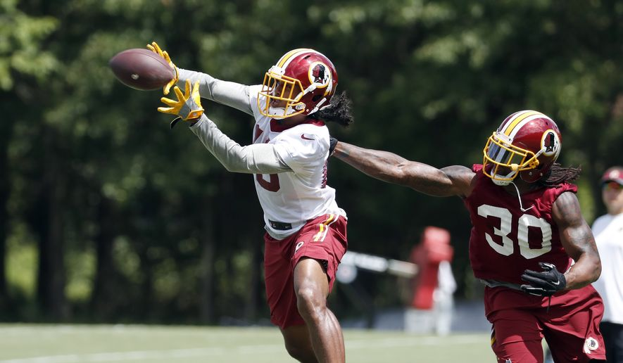 Washington Redskins wide receiver Maurice Harris (13) catches the ball in front of defensive back David Bruton (30) during practice at the team's NFL football training facility at Redskins Park, Wednesday, Aug. 17, 2016 in Ashburn, Va. (AP Photo/Alex Brandon) ** FILE **