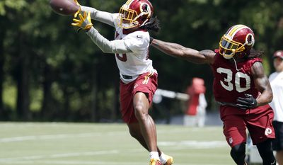 Washington Redskins wide receiver Maurice Harris (13) catches the ball in front of defensive back David Bruton (30) during practice at the team's NFL football training facility at Redskins Park, Wednesday, Aug. 17, 2016 in Ashburn, Va. (AP Photo/Alex Brandon)