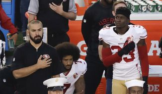 In this Thursday, Sept. 1, 2016, file photo, San Francisco 49ers quarterback Colin Kaepernick, middle, kneels during the national anthem before the team's NFL preseason football game against the San Diego Chargers, in San Diego. (AP Photo/Chris Carlson, File)