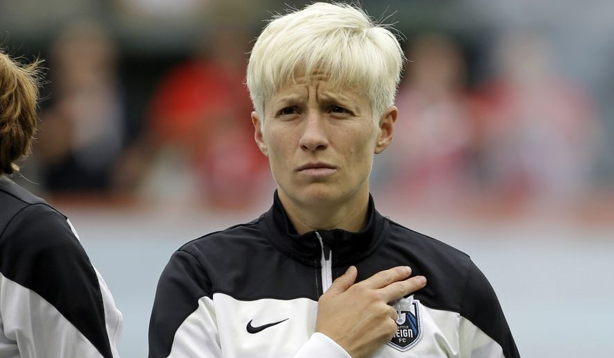 Seattle Reign forward Megan Rapinoe is shown during the national anthem before an NWSL soccer match against the Portland Thorns in Portland, Ore., Wednesday, July 22, 2015. (AP Photo/Don Ryan)