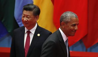 President Obama walks past Chinese President Xi Jinping as he arrives for a group photo session for the G-20 Summit in Hangzhou, China, on Sunday. (Associated Press)