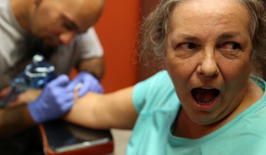 ADVANCE FOR SUNDAY, SEPT. 4, 2016- In this Aug. 18, 2016 photo, Ceil Noworyta looks away from her new tattoo done by Bryan Martinez of The Tattoo Lady in Hammond, Ind., which was created from a Sir Paul McCartney autograph. (Damian Rico/The Times via AP)