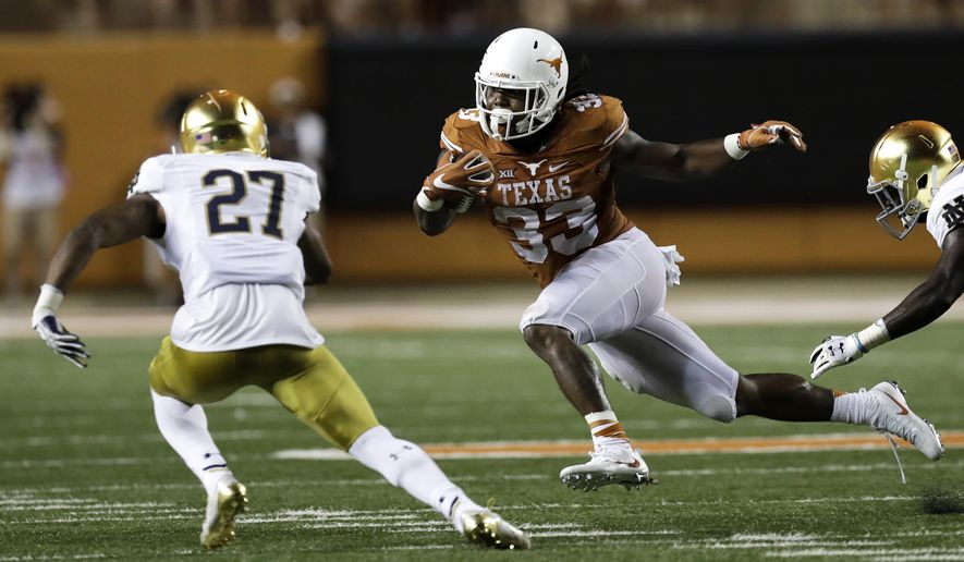 Texas running back D'Onta Foreman (33) runs from Notre Dame cornerback Julian Love (27) during the second half of an NCAA college football game, Sunday, Sept. 4, 2016, in Austin, Texas. (AP Photo/Eric Gay)
