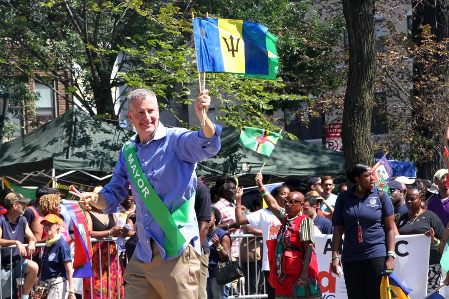 FILE - In this Sept. 7, 2015 file photo, Mayor Bill de Blasio, foreground, makes his way along Eastern Parkway in the Brooklyn borough of New York as he takes part in the West Indian Day Parade.  For years, there have been complaints about safety at J'ouvert  a big, joyous carnival celebrating Caribbean culture held before dawn each Labor Day on the streets of New York City. But after an aide to New York's governor was killed by a stray bullet last year, authorities are taking unprecedented precautions. (AP Photo/Tina Fineberg)