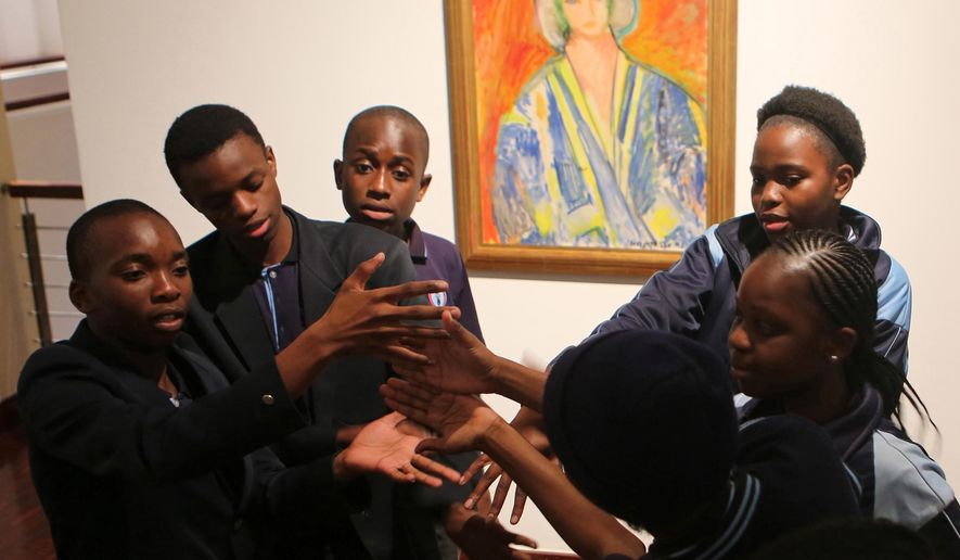 In this photo taken Wednesday Aug. 24, 2016, students from the New Model School pose for a photo in front of a work by artist Henri Matisse in Johannesburg. For the first time, Africa is hosting an exhibit devoted to Henri Matisse. The show in Johannesburg features more than 80 works, including a painting that points to how the continent inspired Matisse and his contemporary, Pablo Picasso. (AP Photo/Denis Farrell)