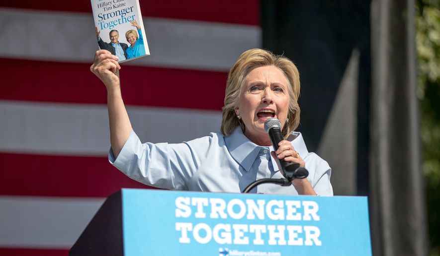 "Democratic presidential candidate Hillary Clinton holds up a book entitled ""Stronger Together"" as she speaks at the 11th Congressional District Labor Day festival at Luke Easter Park in Cleveland, Ohio, Monday, Sept. 5, 2016. (AP Photo/Andrew Harnik)"