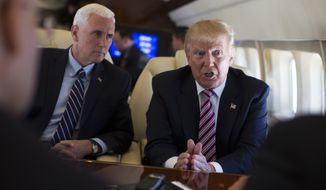 Republican presidential candidate Donald Trump talks with the press, Monday, Sept. 5, 2016, as he flies on board his campaign plane, as Vice presidential candidate Gov. Mike Pence, R-Ind., left, looks on. (AP Photo/Evan Vucci)