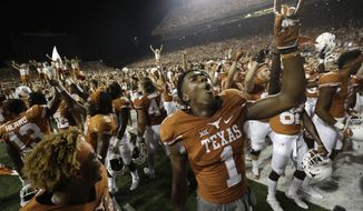 Texas wide receiver John Burt (1) celebrates with teammates after they defeated Notre Dame in double overtime in a NCAA college football game, Sunday, Sept. 4, 2016, in Austin, Texas. Texas won 50-47. (AP Photo/Eric Gay)