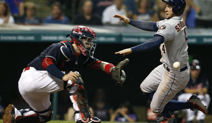 Houston Astros' George Springer (4) scores past Cleveland Indians catcher Roberto Perez (55) on a sacrifice fly by Yulieski Gurriel during the seventh inning of a baseball game Monday, Sept. 5, 2016, in Cleveland. (AP Photo/Ron Schwane)