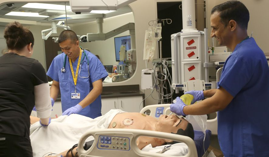 ADVANCE FOR WEEKEND EDITIONS, SEPT. 3-5 - In this Tuesday, Aug.  23, 2016 photo, Dr. Qusay Al Obaidi, center, and Dr. Saad Mijbad, right, work with registered nurse Katie Bush, left, as they intubate and treat a teaching dummy who was set up to simulate a gunshot victim at the Interprofessional Immersive Simulation Center at the University of Toledo Medical College  in Toledo, Ohio. Both doctors are from Iraq and are in the first week of a four week training program in emergency medicine. (Katie Rausch/The Blade via AP)