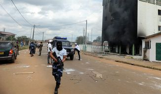 Police stand guard following an election protest in Libreville, Gabon. Post-election violence in Gabon has killed between 50 and 100 people, the opposition presidential candidate said Tuesday, a toll much higher than the government's count. (Associated Press)