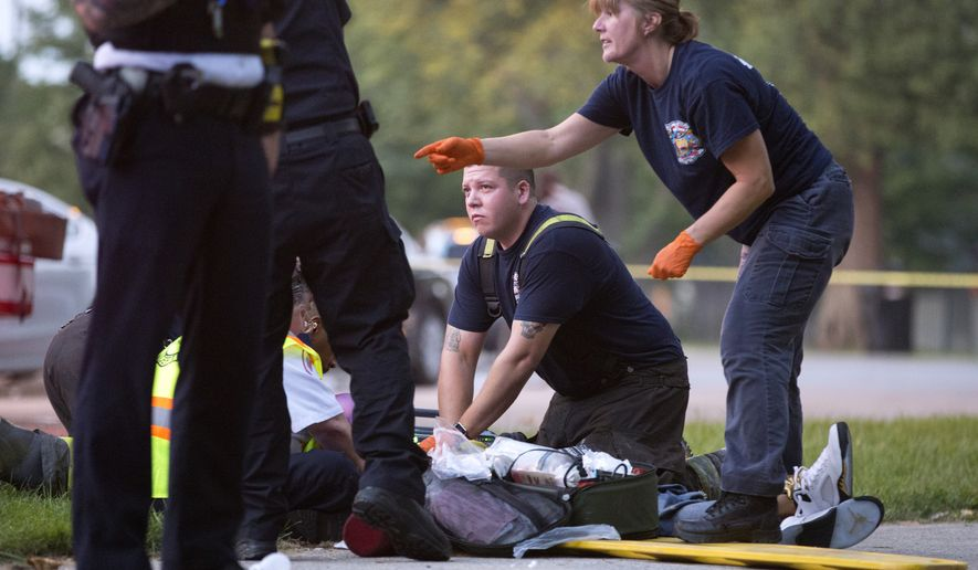 Members of the Chicago Fire Department work on a gunshot victim at the scene of a double shooting in Ogden Park Monday, Sept. 5, 2016, in the Englewood neighborhood of Chicago. Thirteen people were shot to death over the Labor Day weekend in Chicago, making it the deadliest holiday weekend of one of the deadliest summers the city has experienced in decades.  (Erin Hooley/Chicago Tribune via AP) ** FILE **