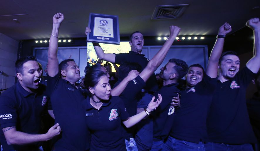 Ahmad Taher, food and beverage manager for Citymax Hotels in Dubai, United Arab Emirates, celebrates with his crew after he won the attempt of world's longest domino drop shot on Monday, Sept. 5, 2016. The hotel's Huddle Sports Bar & Grille in Bur Dubai broke the world record with over 6,000 glasses of energy drink and shots of whiskey under the supervision of an observer from the Guinness Book of World Records. (AP Photo/Kamran Jebreili)