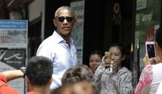 People take photos of U.S. President Barack Obama as he tours a shopping area near the Mekong River in the Luang Prabang, Laos, Wednesday, Sept. 7, 2016. (AP Photo/Carolyn Kaster)
