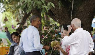U.S. President Barack Obama U.S. Ambassador to Laos Daniel Clune, right, laugh with coconut vendors near the Mekong River the Luang Prabang, Laos, Wednesday, Sept. 7, 2016. (AP Photo/Carolyn Kaster)